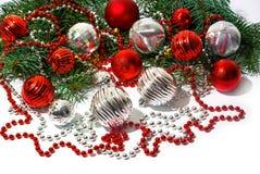 Giocattoli dell'albero di Natale e ramo di albero rossi e d'argento dell'abete su bianco immagini stock libere da diritti