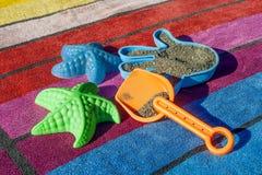 Giocattoli della sabbia su un asciugamano di spiaggia variopinto Immagine Stock Libera da Diritti
