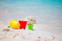Giocattoli della spiaggia del bambino sulla spiaggia sabbiosa bianca Fotografie Stock