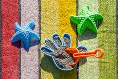 Giocattoli della spiaggia su un asciugamano Fotografie Stock