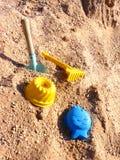 Giocattoli della torta della pala, del rastrello e di sabbia sulla sabbia della sabbiera Fotografia Stock