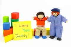 Giocattoli di legno del figlio e di papà con la carta Fotografia Stock