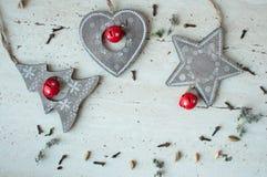 Giocattoli di legno di Natale sulla tavola Albero, cuore, stella e spezie Priorità bassa rustica di natale Immagini Stock