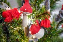 Giocattoli di Natale che appendono sui rami, sotto i regali dell'albero di Natale per Le ghirlande stanno bruciando fotografie stock libere da diritti