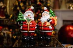 Giocattoli di Natale della porcellana sotto forma di Santa Clous e di pupazzo di neve Immagini Stock