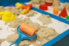 Giocattoli di plastica della muffa con la sabbia sulla sabbiera Immagine Stock