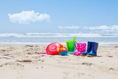 Giocattoli e gumboots di plastica sulla sabbia della spiaggia Immagine Stock