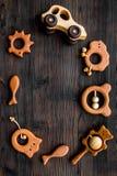 Giocattoli fatti a mano di legno svegli per neonato sul copyspace di legno scuro di vista superiore del fondo Fotografia Stock
