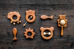 Giocattoli fatti a mano di legno svegli per neonato sulla vista superiore del fondo di legno scuro Fotografie Stock