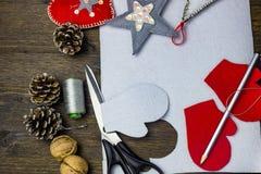 Giocattoli luminosi di Natale fatti di feltro Forbici, matita, filo ed urti su una tavola di legno Fotografia Stock