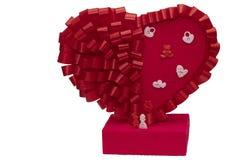 Giocattoli per gli uomini e le donne accanto ad un grande cuore rosso su un fondo bianco Le figurine della famiglia si chiudono s fotografia stock