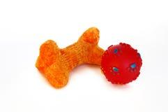 Giocattolo arancione dell'osso di cane e sfera rossa Immagini Stock