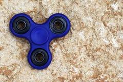 Giocattolo blu di alleviamento di sforzo del FILATORE di irrequietezza su fondo di pietra È Fotografie Stock