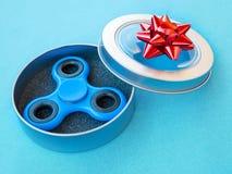 Giocattolo colourful popolare del filatore di irrequietezza in un contenitore di regalo su un fondo colorato Fotografia Stock