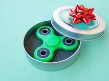 Giocattolo colourful popolare del filatore di irrequietezza in un contenitore di regalo su un fondo colorato Fotografie Stock
