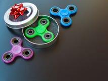 Giocattolo colourful popolare del filatore di irrequietezza in un contenitore di regalo su un fondo nero Fotografia Stock