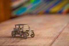 Giocattolo d'annata del veicolo per il trasporto del metallo con i libri variopinti su uno scaffale Immagini Stock Libere da Diritti