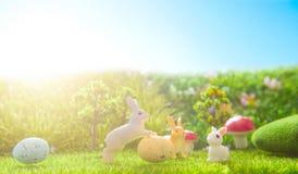 Giocattolo dei conigli di Pasqua sull'erba verde della molla Ambiti di provenienza astratti di fantasia con il libro magico Immagine Stock