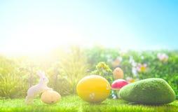 Giocattolo dei conigli di Pasqua sull'erba verde della molla Ambiti di provenienza astratti di fantasia con il libro magico Fotografia Stock