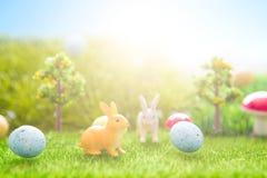 Giocattolo dei conigli di Pasqua sull'erba verde della molla Ambiti di provenienza astratti di fantasia con il libro magico Fotografie Stock