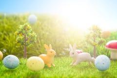 Giocattolo dei conigli di Pasqua sull'erba verde della molla Ambiti di provenienza astratti di fantasia con il libro magico Immagini Stock Libere da Diritti