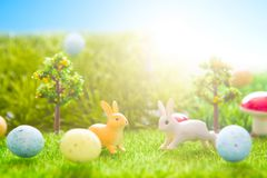 Giocattolo dei conigli di Pasqua sull'erba verde della molla Ambiti di provenienza astratti di fantasia con il libro magico Fotografie Stock Libere da Diritti