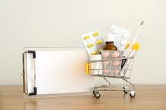 Giocattolo del carrello con i medicinali e la nota della carta: pillole, blister, bottiglie mediche, termometro ed insieme di ric immagini stock