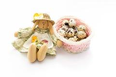 Giocattolo del coniglietto di pasqua vicino al canestro rosa con le uova di quaglia su fondo bianco Immagine Stock