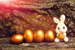 Giocattolo del coniglio, uova di Pasqua dorate sul fondo della corteccia di albero Immagine Stock