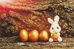 Giocattolo del coniglio, uova di Pasqua dorate sul fondo della corteccia di albero Fotografia Stock Libera da Diritti
