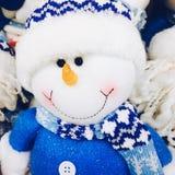 Giocattolo del pupazzo di neve vestito in sciarpa e cappuccio fotografia stock