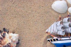 Giocattolo della nave e di Shell sulla sabbia Fotografie Stock Libere da Diritti
