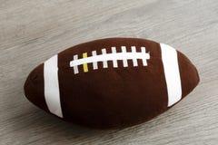 Giocattolo della palla di rugby per i bambini sul pavimento di legno Fotografia Stock