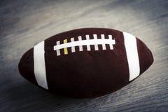 Giocattolo della palla di rugby per i bambini sul pavimento di legno Fotografie Stock Libere da Diritti