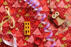 Giocattolo di legno della casa e del gufo e serpantine viola con i nastri variopinti sull'involucro festivo come decorazione del  Fotografia Stock