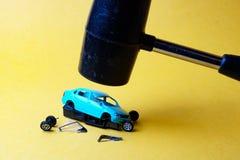 Giocattolo di modello ripartito dell'automobile blu sopra cui ha appeso il nero del martello fotografia stock libera da diritti