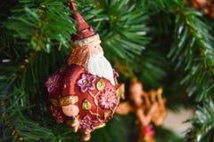 Giocattolo di natale del Babbo Natale sull'albero di Natale artificiale Fotografia Stock