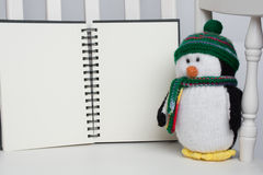 Giocattolo farcito del pinguino sulla sedia di oscillazione bianca con il libro in bianco Immagine Stock Libera da Diritti