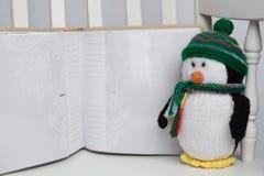 Giocattolo farcito del pinguino sulla sedia di oscillazione bianca con l'album di foto Fotografia Stock Libera da Diritti