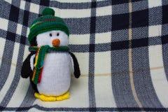 Giocattolo farcito pinguino sulla coperta blu del plaid Immagine Stock Libera da Diritti