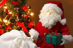 Giocattolo farcito sveglio Santa Claus che dà un regalo di Natale. Fotografia Stock Libera da Diritti