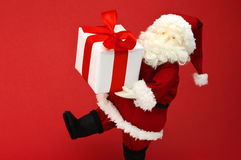 Giocattolo farcito sveglio Santa Claus che porta grande regalo di Natale. Fotografia Stock Libera da Diritti