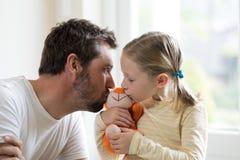 Giocattolo molle baciante della figlia e del padre fotografia stock