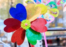 Giocattolo multicolore della girandola con il fiore sulla spiaggia fotografia stock libera da diritti