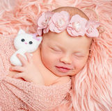 Giocattolo neonato adorabile della tenuta della ragazza sulla coperta lanuginosa rosa Fotografie Stock Libere da Diritti