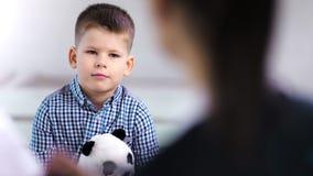 Giocattolo pensieroso della tenuta del ragazzo del piccolo bambino al primo piano di medium di sessione di psicoterapia del bambi stock footage
