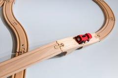 Giocattolo rosso del treno sulla pista di legno di plastica su bianco Fotografie Stock