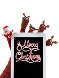 Giocattolo Santa Claus di concetto di Natale e renna con un touchpad del regalo a disposizione Fotografia Stock