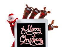 Giocattolo Santa Claus di concetto di Natale e renna con un touchpad del regalo a disposizione Immagini Stock