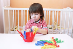 Giochi adorabili del ragazzino con le mollette per il bucato Immagine Stock